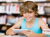 Escolar primario con la tableta en biblioteca Fotografía de archivo