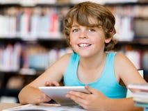 Escolar primario con la tableta en biblioteca Imagen de archivo