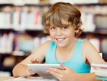 Escolar primario con la tableta en biblioteca Fotografía de archivo libre de regalías