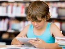 Escolar primario con la tableta en biblioteca Imágenes de archivo libres de regalías