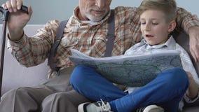 Escolar que aprende el mapa del mundo con la ayuda de abuelo, pensionista que comparte conocimiento almacen de metraje de vídeo