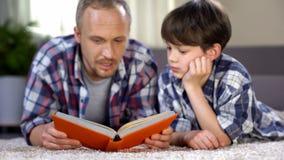 Escolar que escucha el papá que lee el libro emocionante de la aventura, amor a la literatura imagen de archivo
