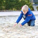 Escolar que juega con la arena en el patio Fotografía de archivo libre de regalías