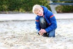 Escolar que juega con la arena en el patio Imagenes de archivo