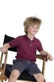 Escolar que se sienta en la silla del director sobre el fondo blanco Imagenes de archivo