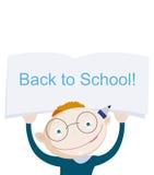 Escolar rojo sonriente del pelo que muestra el cuaderno con frase del saludo de nuevo a escuela Imagen de archivo