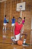 Escolar sonriente que se arrodilla con un baloncesto mientras que equipo que juega en fondo Imagen de archivo libre de regalías
