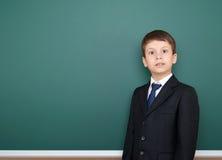 Escolar sorprendido en retrato negro del traje en el fondo verde de la pizarra, concepto de la educación Fotografía de archivo