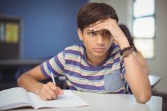 Escolar tensado que hace la preparación en sala de clase Foto de archivo libre de regalías