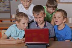 Escolares con el ordenador portátil Imágenes de archivo libres de regalías