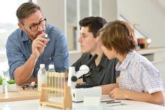 Escolares con el profesor en química Foto de archivo libre de regalías