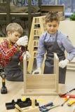 Escolares jovenes que aprietan los tornillos en taburete de madera Fotografía de archivo