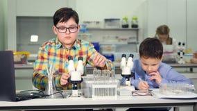 Escolares que hacen experimentos de la ciencia en laboratorio de la escuela almacen de video