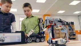 Escolares que hacen los robots hecho a sí mismos en el laboratorio de la escuela de ingeniería almacen de video