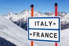 Escolha de Itália ou de França ao esqui ou ao snowboard Sinal da informação em picos de montanha do inverno sob o fundo do céu az fotos de stock