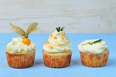Escolha de três queques em um azul de madeira Foto de Stock
