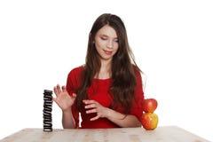 Escolha dura. A menina não sabe o que comer Fotografia de Stock Royalty Free