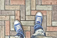 A escolha, escolhas Conceito: O começo do trajeto, a escolha do sentido Vista de acima Pés nas sapatilhas azuis no pa Imagens de Stock