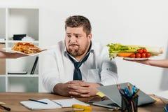 escolha gorda do homem de negócios saudável ou comida lixo no local de trabalho foto de stock