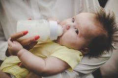 Escolha a mãe nova que alimenta seu bebê pequeno em casa imagem de stock