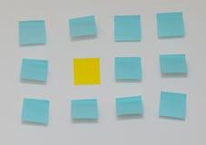Escolha a nota de post-it amarela no mar de notas de post-it azuis Imagem de Stock Royalty Free