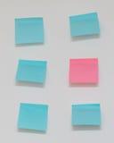 Escolha a nota de post-it cor-de-rosa no mar de notas azuis do cargo Imagem de Stock