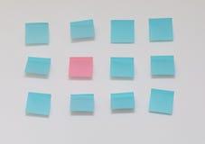 Escolha a nota de post-it cor-de-rosa no mar de notas de post-it azuis Fotos de Stock Royalty Free