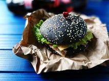 Escolha o espeto preto dos Hamburger sob a forma dos corações em um fundo de madeira azul Imagens de Stock