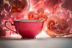 Escolha a xícara de chá vermelha em um fundo floral cor-de-rosa fotografia de stock