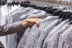 Escolhas que da mulher uma lã reveste em ganchos na loja imagem de stock
