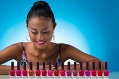 Escolhendo a cor do verniz para as unhas Fotos de Stock Royalty Free