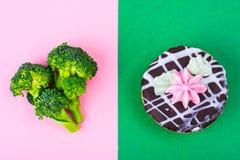 Escolhendo entre brócolis e o alimento insalubre, arbusto do bolo Conceito do vegetarianismo e do estilo de vida saudável foto de stock royalty free