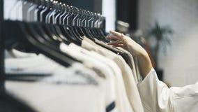 Escolhendo a roupa comprar em uma loja Fotos de Stock Royalty Free