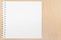 Esconda el cuaderno abierto en la tabla Tabla de la oficina con la libreta Fotos de archivo