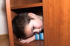 Esconder assustado da criança imagens de stock