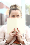 Esconder atrás de um livro Imagens de Stock Royalty Free