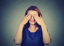 esconder Olhos tímidos de sorriso da coberta da mulher Fotos de Stock
