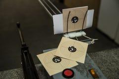 Escopeta de aire comprimido y tres blancos con los agujeros de bala en ella Imagen de archivo libre de regalías