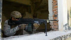 Escopeta marina del montaje del soldado en la ventana para defender el edificio arruinado almacen de video