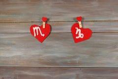 Escorpião e Capricórnio sinais do zodíaco e do coração CCB de madeira fotografia de stock royalty free