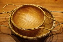 Escorredores de bambu tecidos estilo do vintage isolados na tabela de madeira fotografia de stock royalty free