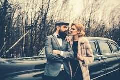 Escort of girl by security. Bearded man and sexy woman in coat. Travel and business trip or hitch hiking. Couple in love. Escort of girl by security. Bearded men royalty free stock photo