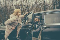 Escort of girl by security. Bearded man and woman in fur coat. Couple in love on romantic date. Retro collection. Escort of girl by security. Bearded men and stock photo