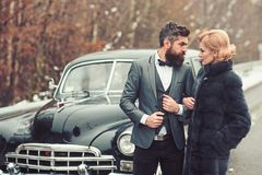 Escort of girl by security. Couple in love on romantic date. Bearded man and sexy woman in fur coat. Retro collection. Escort of girl by security. Couple in love stock photography