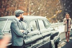 Escort of girl by security. Retro collection car and auto repair by mechanic driver. Bearded man and sexy woman in fur. Escort of girl by security. Retro royalty free stock images