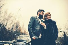 Escort of girl by security. Retro collection car and auto repair by mechanic driver. Travel and business trip or hitch. Hiking. Bearded men and sexy women in royalty free stock photo