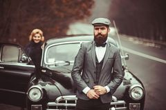 Escort of girl by security. Retro collection car and auto repair by mechanic driver. Travel and business trip or hitch. Hiking. Couple in love on tic date stock image
