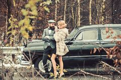 Escort of girl by security. Travel and business trip or hitch hiking. Bearded man and sexy woman in fur coat. Retro. Escort of girl by security. Travel and stock photography