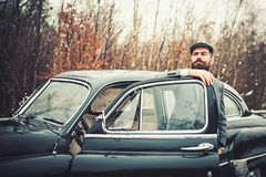 Escort man or security guard. Bearded man in car. Call boy in vintage auto. Retro collection car and auto repair by. Mechanic driver. Travel and business trip royalty free stock image