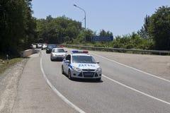 Escort of police cars on road. Chemitokvadzhe, Caucasus, Russia. Lazarevskoe, Sochi, Krasnodar region, Russia - July 1, 2014: Escort of police cars on road Stock Image